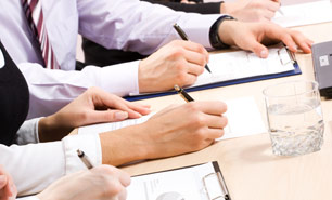 Dedicated group of employment law professionals write on clipboards in a meeting