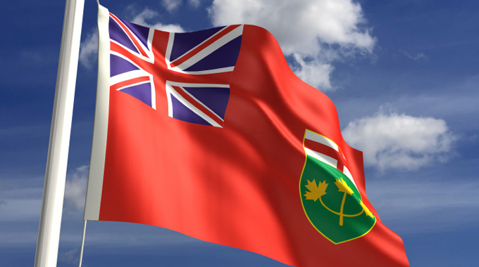 The Provincial flag of Ontario's blows in the wind against a backdrop of blue sky and white clouds