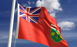 The Province of Ontario's flag blows in the wind against a backdrop of blue sky and white clouds